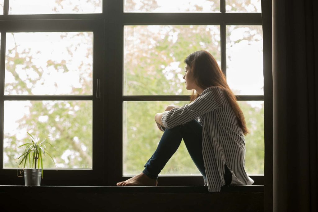 Thoughtful girl sitting on sill embracing knees looking at ...